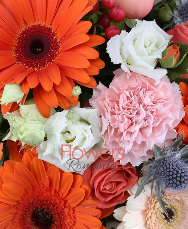 5 gerbera portocalii, 5 gerbera crem, 5 garoafe roz, 3 lisianthus alb, 7 trandafiri portocalii, 3 eryngium, 3 hypericum roșu, 3 miniroze portocalii, cub sticla