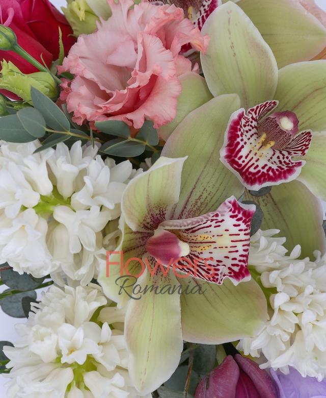 3 trandafiri rosii, 3 zambile albe, 3 frezii mov, 4 lalele mov, 2 lisianthus roz, cymbidium verde, eucalypt, coș