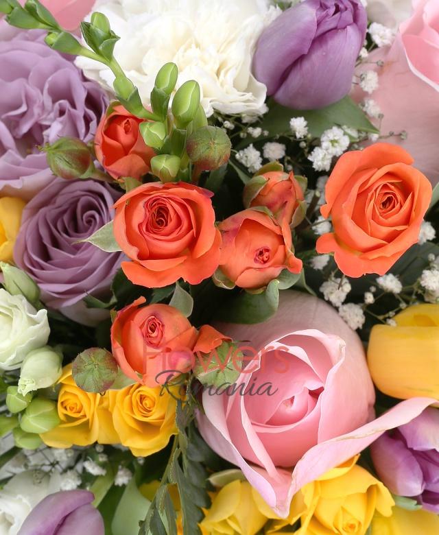 10 lalele mov, 5 lalele galbene, 3 miniroze portocalii, 5 garoafe albe, 3 trandafiri roz, 2 trandafiri mov, 3 miniroze galbene, 10 frezii albe, 3 lisianthus alb, gypsophila, eucalypt, ferigă