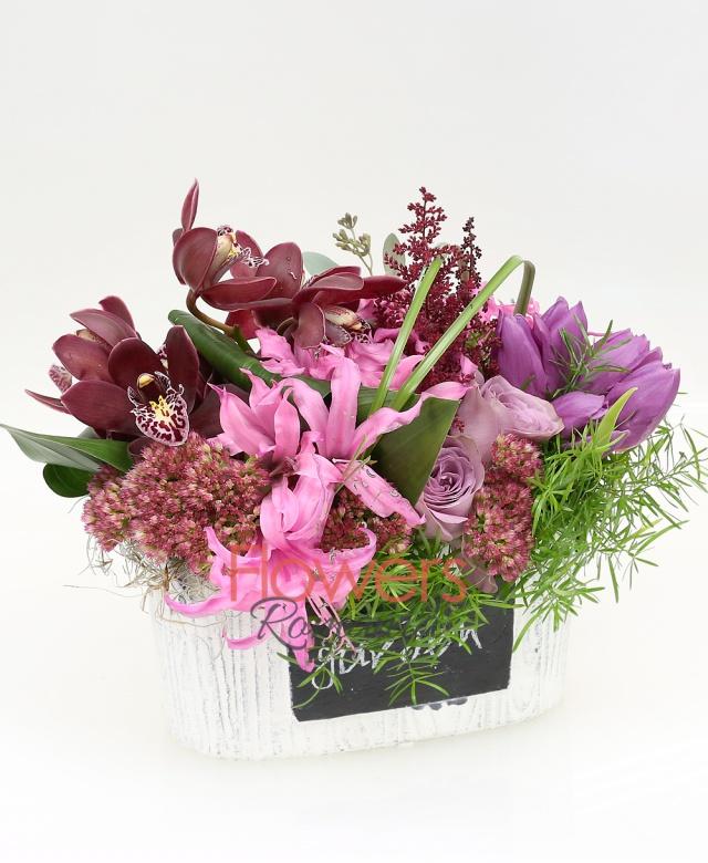 ceramic pot, 2 purple roses, 5 purple tulips, 5 nerine, burgundy cymbidium cups, 3 kalanchoe, 3 burgundy astilbe, waxflower, greenery
