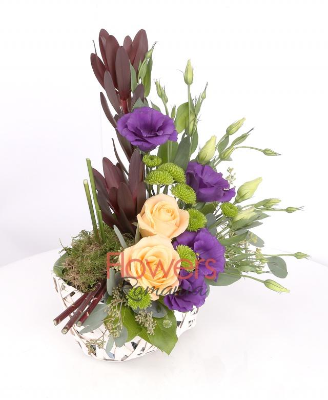 wicker basket, 2 banana roses, 2 leucadendron, 3 purple lisianthus, 2 green santini, greenery
